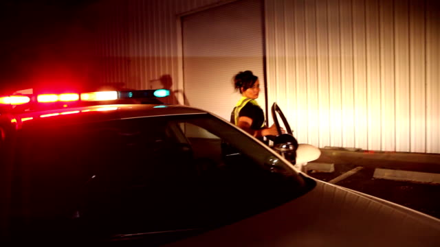 Policewoman exits police car with flashing lights, runs
