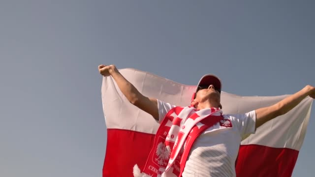 polish football fan in his 30s running with polish national flag in slow motion - polonia video stock e b–roll