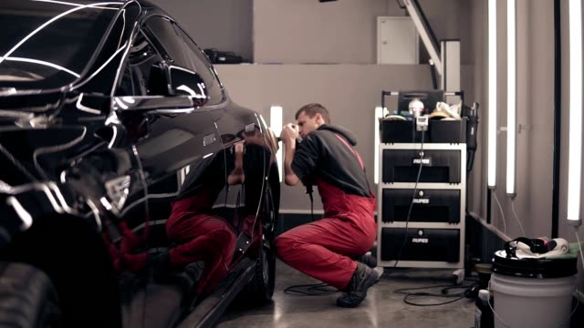 Polishing car with polish mashine. Worker in red suit cleaning a black expensive car. video