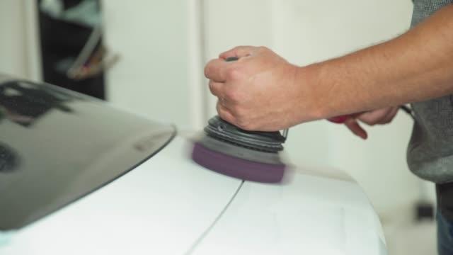 polieren der karosserie mit einem manuellen automatischen schleifer mit wachs und polierpaste - wachs epilation stock-videos und b-roll-filmmaterial
