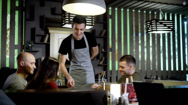 polite waiter is helping to company of friends to choose meals from menu in a restaurant in dinner hour polite waiter is helping to company of friends to choose meals from menu in a restaurant in dinner hour, at a Christmas Holidays wait staff stock videos & royalty-free footage