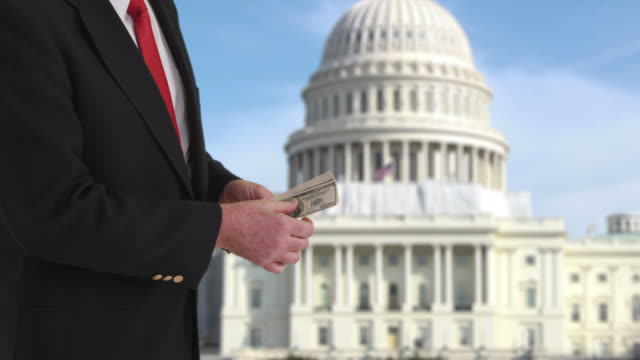 Politician counting money in front of US Capitol building video