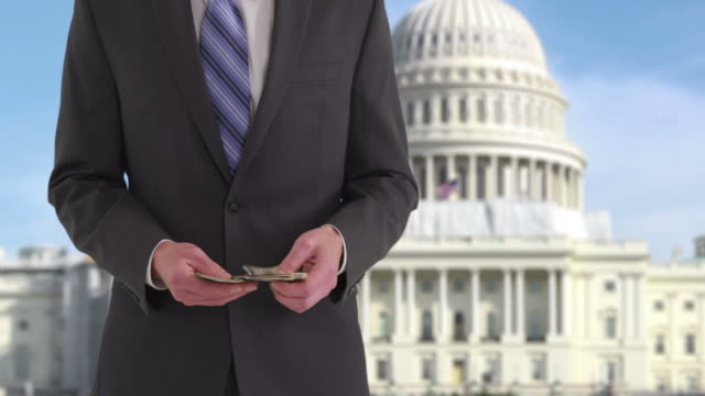 politician with money in front of us capitol building - politician stock videos and b-roll footage
