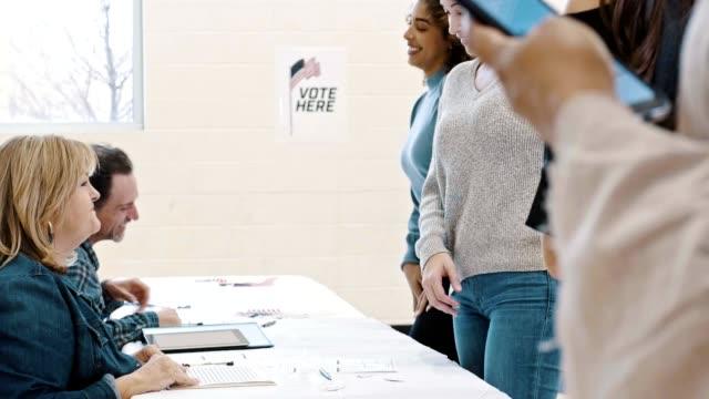 投票所のボランティアは、選挙の日に有権者を支援します - 選挙点の映像素材/bロール