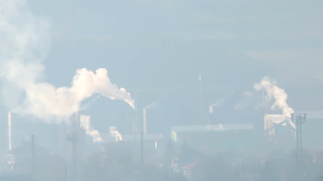 Polluting factory, dusty air over industrial buildings video