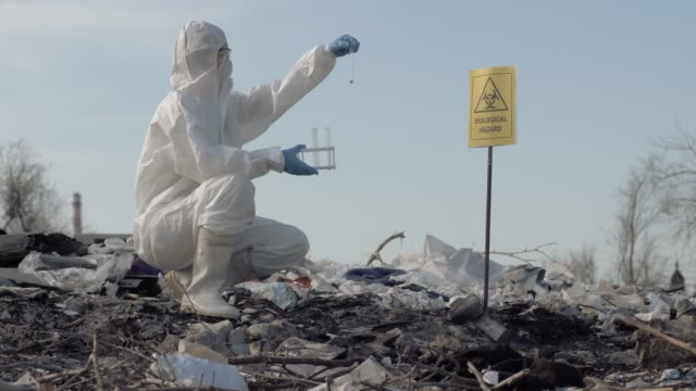 pollution environmental, woman scientist in uniform and protective gloves holding test tubes and taking sample of the garbage from big dirty landfill near sign biological hazard