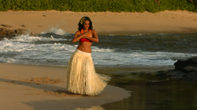 Polynesian hula dancer performs by ocean, slow motion video