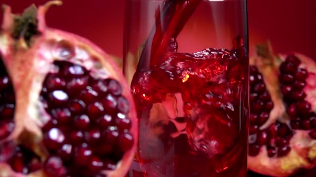 Pomegranate juice is flowing into a jug next to the ripe halves of pomegranates - video