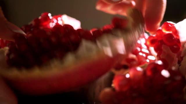vídeos de stock e filmes b-roll de romã peças e mulher mãos macro plano charriot - romã