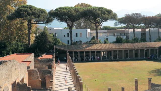pompeii, italya. i̇nsanlar turistler sunny day antik bina kuadrisuna remains yakın yürüme. unesco dünya mirası - unesco stok videoları ve detay görüntü çekimi