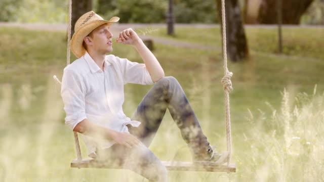 stockvideo's en b-roll-footage met slo mo ds peinzen jongeman zit op een schommel - stro