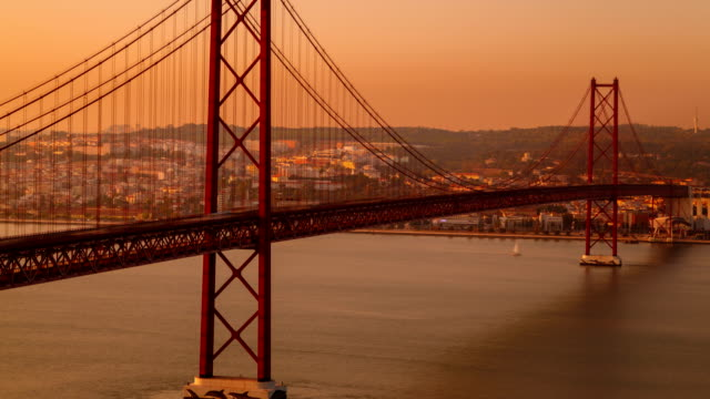 Ponte 25 de Abril bridge, Lisbon, Portugal A dusk timelapse of the Ponte 25 de Abril suspension bridge in Lisbon, Portugal. The bridge, which connects Lisbon to Almada on the southbank of the Tagus, can be seen buckling as traffic passes by ponte 25 de abril stock videos & royalty-free footage
