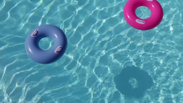 stockvideo's en b-roll-footage met pool hoepels zwevend in water - opblaasband