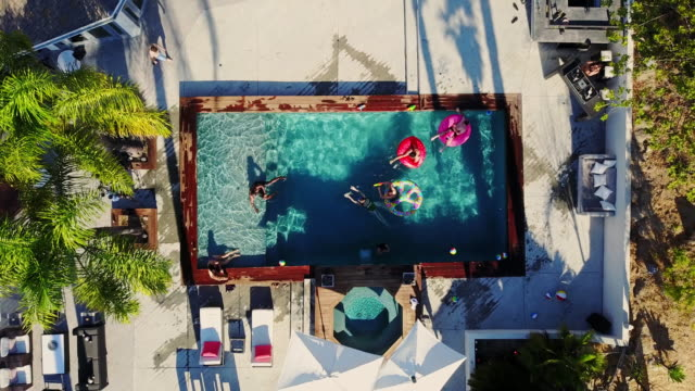 Pool Party Seen from a Drone Top down drone shot flying across a backyard where a group of people are playing around and floating on inflatables, while others are drinking around an outdoor bar. pool party stock videos & royalty-free footage