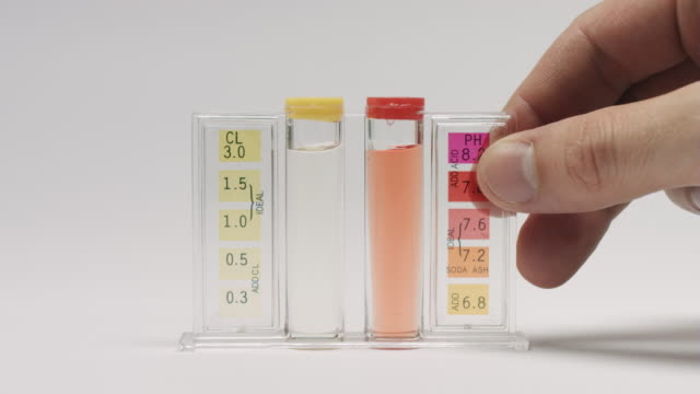 Pool water test results Pool water test results, close up of hand put test tubes with chlorine and ph water test indicators on white background surface chlorine stock videos & royalty-free footage