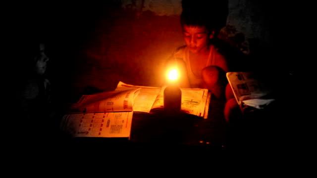Poor children reading under lantern light video