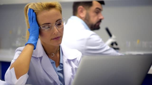 Poor female researcher struggling with severe headache at work video