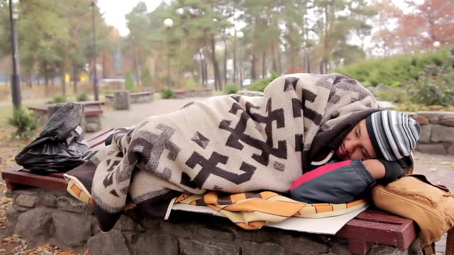 Poor homeless male lying on bench in cold city park covered with old blanket video
