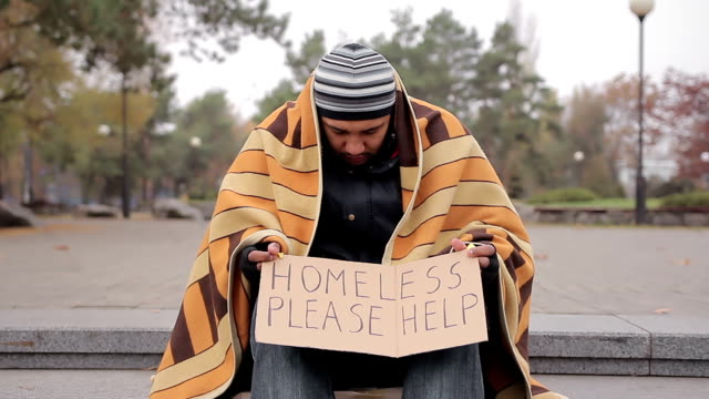 Poor homeless man sitting in cold street with help sign, begging for charity video