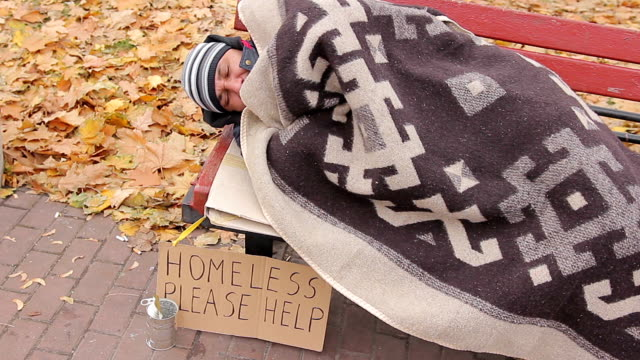 Poor homeless person lying on bench, beggar feeling sick, coughing from cold video