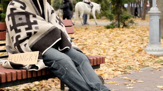 Poor homeless person sitting on bench with hungry sign, begging for spare change video
