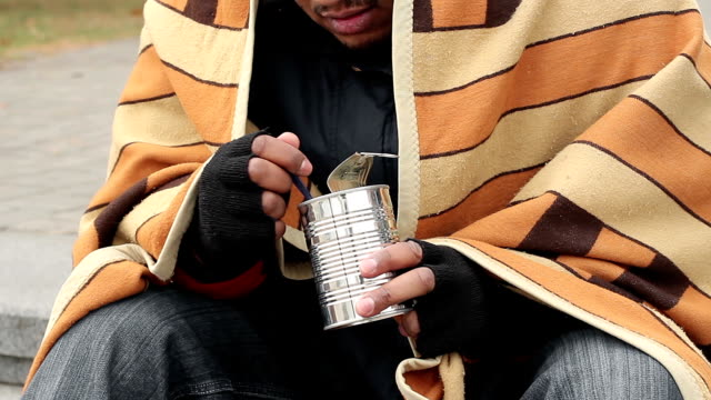 Poor hungry guy eating canned food, thinking about life, poverty, homelessness video