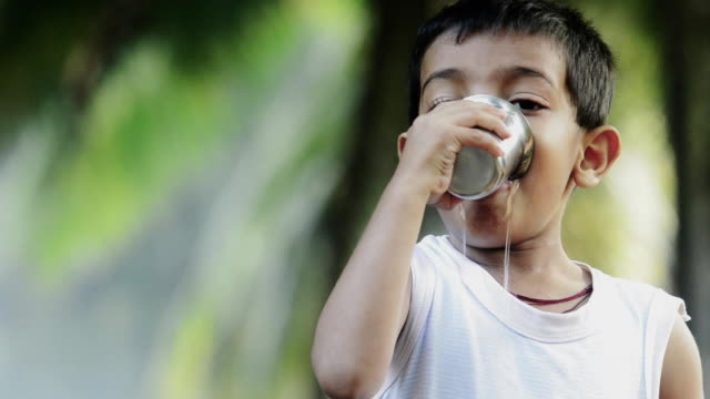 poor Indian little boy drinking water with steelglass video
