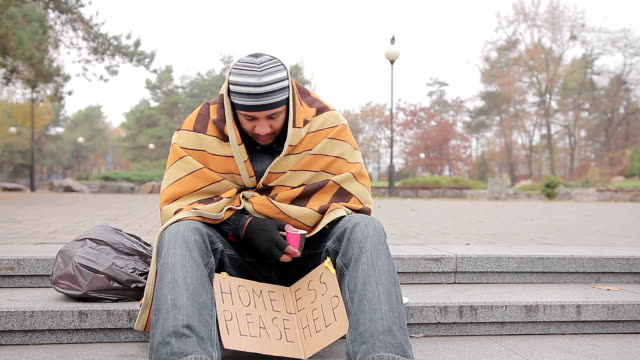 Poor man asking for charity in city park, miserable homeless person needs help video