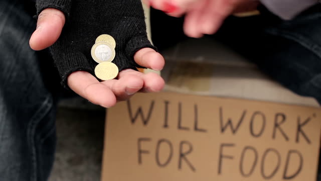 Poor man begging for change, holding coins in his hands, will work for food sign video