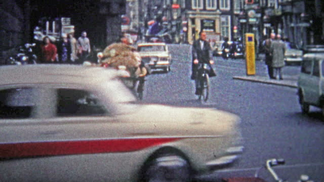 COLOGNE, GERMANY - 1966: A poor man biking a large quantity of unknown goods across town.