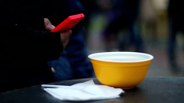 Poor man having cheap meal at street snack bar, texting video