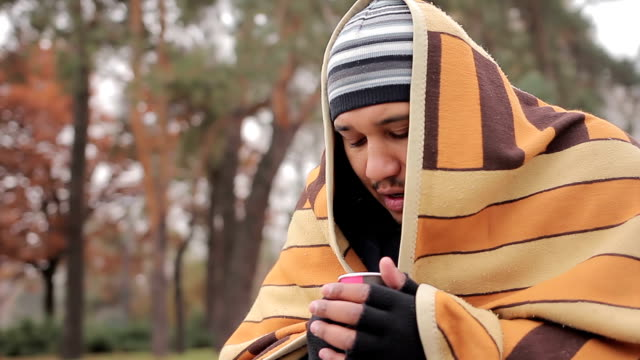 Poor man with sad face hiding from cold in shabby blanket, warming with hot tea video