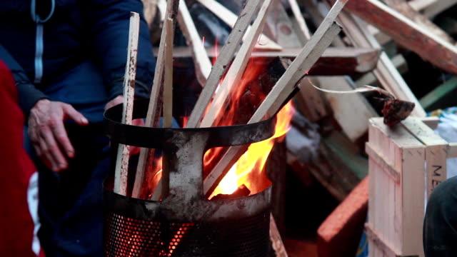 Poor people burn wood trash bin barrel to warm, winter video