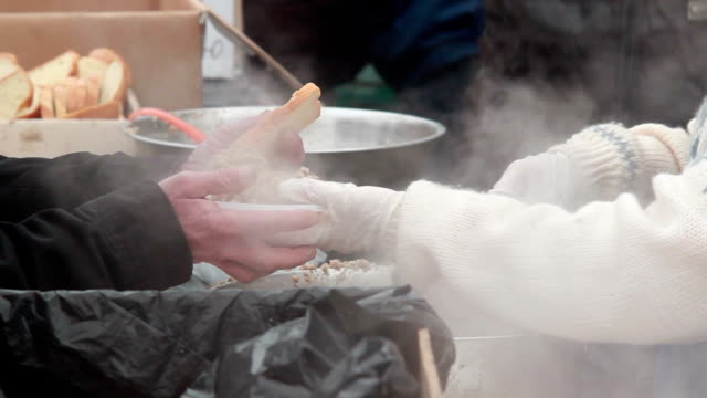 Poor people receive meal eating outdoors winter city food giving video