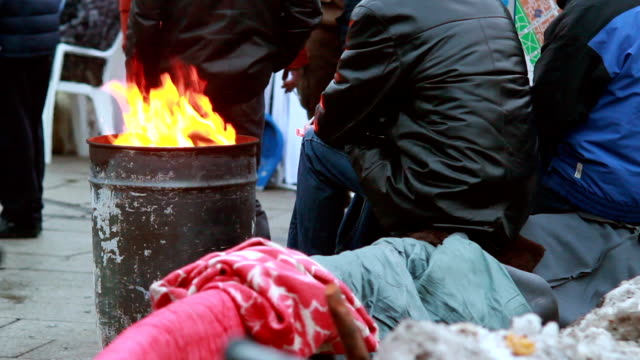 poor people warming near fire trash barrel, winter outdoors - homelessness stock videos & royalty-free footage