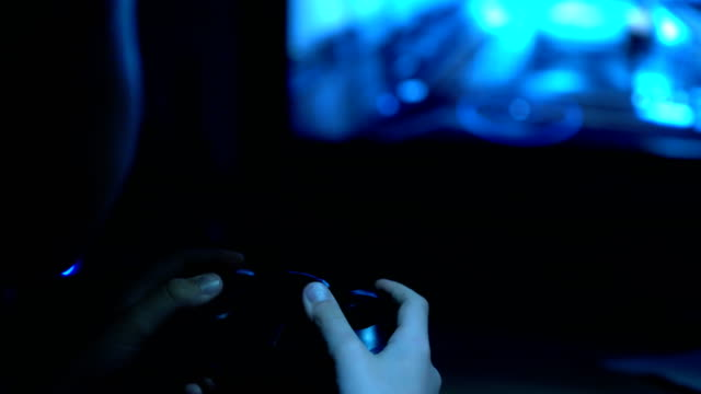 4k poorly-lit footage of boy holding joystick in hand - telecomando background video stock e b–roll