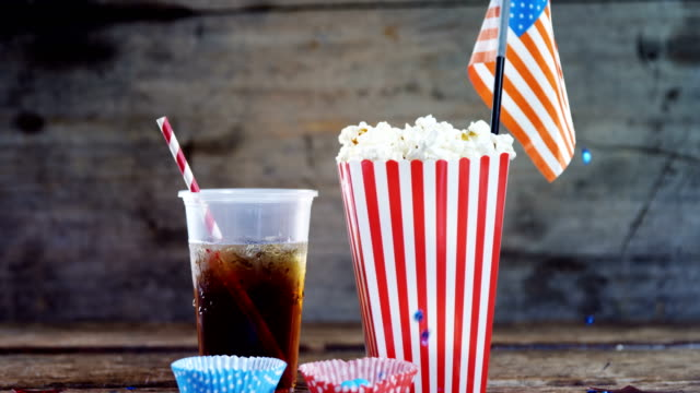 Popcorn, confectionery and drink on wooden table video