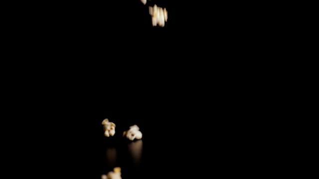 vídeos de stock, filmes e b-roll de fim da queda da pipoca acima. as partes brancas de pipoca caem no movimento lento um fundo preto e saltam fora de se. closeup. - balde pipoca
