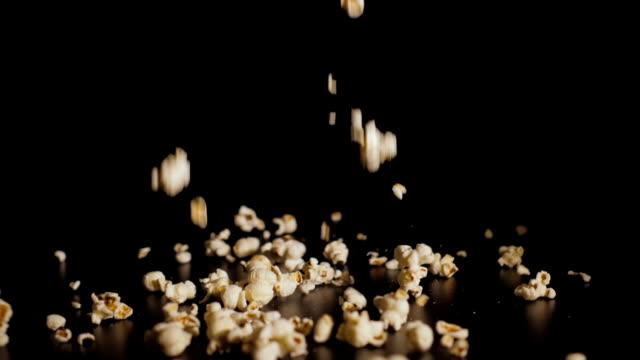 vídeos de stock, filmes e b-roll de pipoca que cai perto acima. as partes brancas de pipoca caem no movimento lento um fundo preto e saltam fora de se. closeup. - balde pipoca
