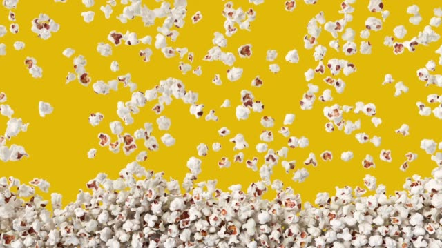 Popcorn falling down from top, fast food background texture pattern. Salty tasty pop corn on yellow background. snack stock videos & royalty-free footage