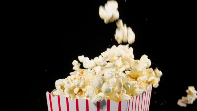 stockvideo's en b-roll-footage met popcorn die in slow motion in een popcorn emmer valt - popcorn