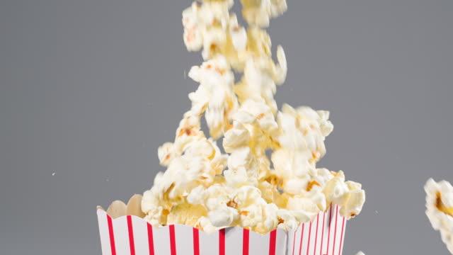 popcorn falling in slow motion into a popcorn bucket - готовый к употреблению стоковые видео и кадры b-roll