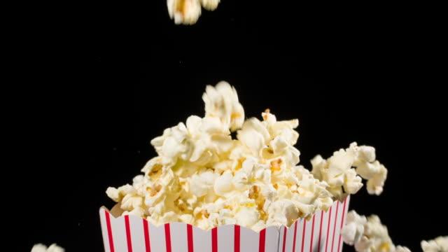 vídeos de stock, filmes e b-roll de pipoca que cai no movimento lento em um balde da pipoca - balde pipoca