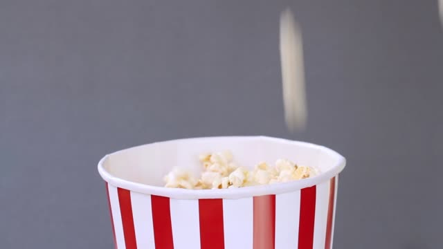 vídeos de stock, filmes e b-roll de pipoca cair no balde vermelho e branco listrado em fundo cinza. - balde pipoca