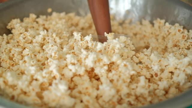 vídeos de stock, filmes e b-roll de pipoca de caramelo de mistura. - balde pipoca