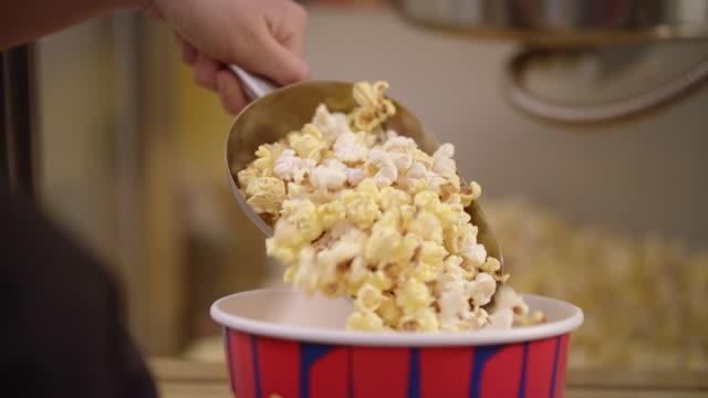 stockvideo's en b-roll-footage met popcorn gieten in container met pollepel in slow motion. - popcorn