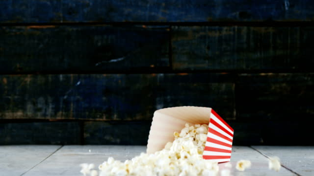Popcorns falling on wooden table video