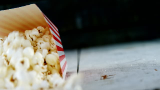 Popcorns spilled on wooden table video