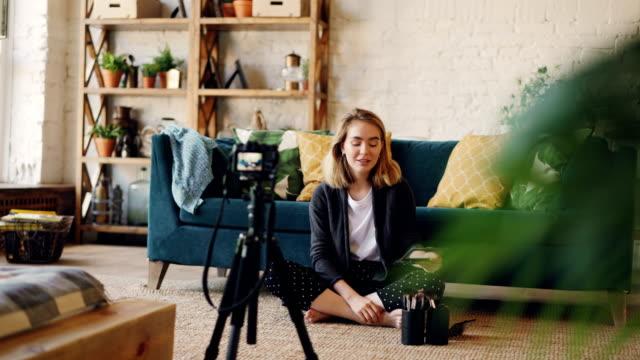populära kvinnliga bloggare videoinspelning om smink och skönhet sitter på golvet hemma och med kameran på stativ. flickan är visar kosmetika kit och med borste. - makeup artist bildbanksvideor och videomaterial från bakom kulisserna
