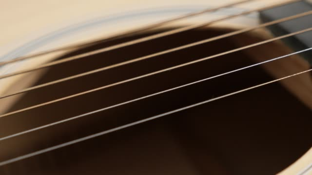 Popular wooden acoustic guitar strings shallow DOF 4K 2160p 30fps UltraHD panning footage - Details of string instrument body slow pan 3840X2160 UHD video